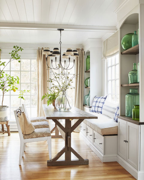 The designer's home is filled with subtle pops of green and blue, like the indigo print breakfast nook pillows in her kitchen, which the couple remodeled in 2010. As part of the overhaul, she took down a wall that divided it from the adjacent dining room, added windows, and installed lots of reclaimed wood shelves. By the sink, she keeps dishware, bread boards, and potted herbs in view and within reach; on each side of her breakfast nook, she displays her collection of blue and green demijohn bottles.   Ideas to create a Rural Farmhouse neutral home dining room 0415