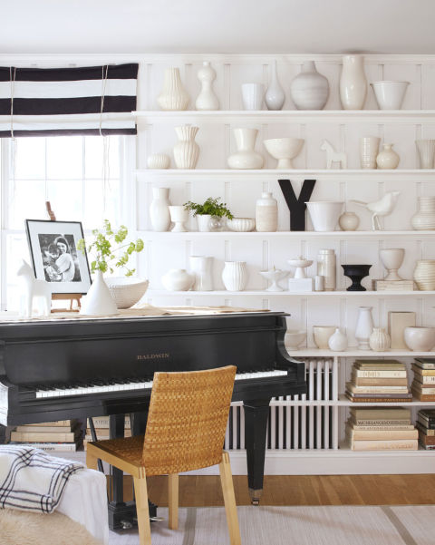 "Even many of Ingrid's accessories are white, such as her vast collection of pottery on display in the living room. ""As a ceramics major in college, I started collecting white pottery,"" she says. ""The wall with the collection is more dynamic than it might seem, thanks to the pieces' different shapes, shades, and eras.""   Ideas to create a Rural Farmhouse neutral home shelving 0415"