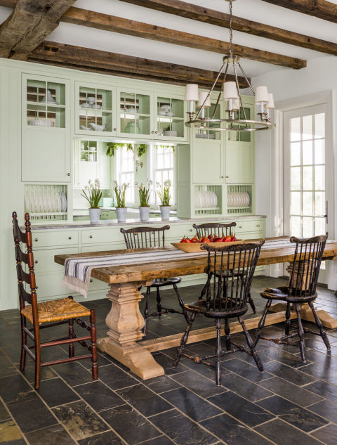 For the ultimate farmhouse-style breakfast room, this homeowner mixed a hefty trestle-base table with antique ladder-back and Windsor chairs and a polished nickel chandelier that evokes equestrian tack supply.<br />