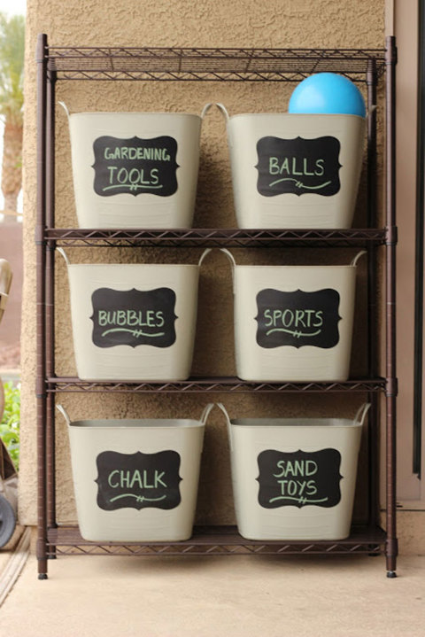 Keep your yard clutter-free by placing bins with adhesive chalkboard labels onto a sturdy bronze shelf. Get the tutorial at Moosha Girl.