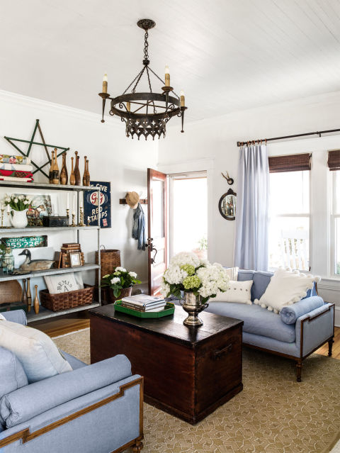 A midcentury pair of salvaged sofas cost a mere $100 on Craigslist—an upholsterer replaced the dated floral pattern with a soft, affordable blue Oxford cloth. For added charm in this North Carolina farmhouse, collected vintage finds decorate an industrial shelving unit.