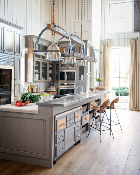 "Ronnie enlisted Nashville designer Rachel Halvorson to add a layer of refinement to the rustic home. First up: the kitchen, where an abundance of moody gray cabinetry, limestone countertops, and stainless steel appliances add luxe elements to the rough-hewn space. There, Rachel also introduced a key part of her design for the house: light fixtures that up the wow factor in each room. Starting with three 16"" polished nickel pendants, she designed a custom pulley framework for them using barnwood and steel. The final product is a sleek showpiece that can hold its own above the 13-foot-long kitchen island. In this photo: To maximize storage, one half of the island contains a series of baskets and bins; the other half has an additional work surface mounted with coasters to roll away when not in use."