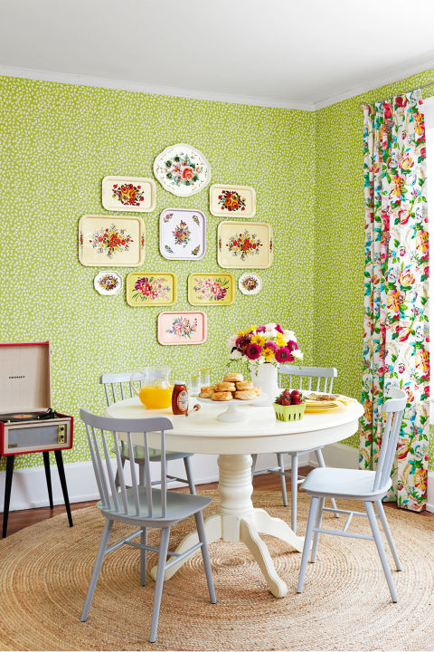 Cultivate an indoor vertical garden with a rambling vine wallpaper. The small-scale pattern provides a muted enough backdrop for bolder statement pieces, like vintage metal trays featuring bold buds. A quartet of soft gray Windsor chairs and an heirloom-worthy pedestal table balance the pattern play on the walls.<br />