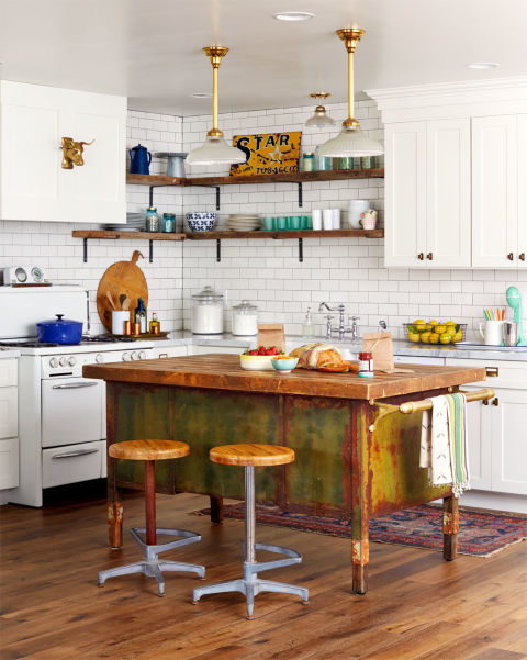 A wood and metal military desk-turned-prep island is the centerpiece of this Arizona ranch home's kitchen. The weathered wood top and rusty green base give the kitchen more personality. Barnwood shelves pick up the warmth of the island's counter, while brass pendants (from an old ice-cream parlor) echo the towel bar's shine.