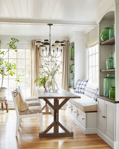 Subtle pops of green and blue, like the indigo print breakfast nook pillows, keep the dining room in this rural Connecticut farmhouse bright. The homeowner displays her collection of blue and green demijohn bottles on either side of the dining room table in built in shelves.<br />
