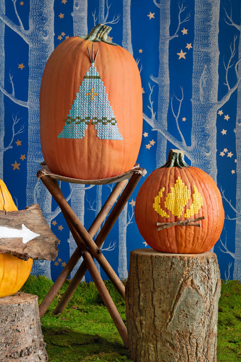 Add homespun charm to your decor with our tepee and campfire. Download and print our cross-stitch patterns. (Adjust pattern size as needed.) Tape onto artificial, carvable pumpkins (store.funkins.com). (Trust us: You'll want to display these year after year.) Punch through the pattern's cross-stitch points with an awl (walmart.com). Use a jab saw (homedepot.com) to cut an opening in the bottom of both pumpkins large enough for your hand to work inside. Cross-stitch using a tapestry needle and yarn (Lion Brand Yarn in Seaspray, Oliveish, and Mustard; joann.com). For tepee support poles and campfire logs, adhere twigs with hot-glue.