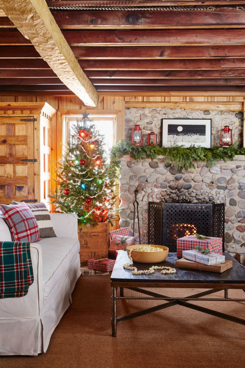 For the tree in this cozy Christmas cabin, a simple popcorn garland, glass ball ornaments, and a wooden crate in lieu of a tree skirt reinforce the home's-stuck-in-time vibe. The fir garland above the mantel and solo sprigs of pine found in vases throughout the house also add an organic element.