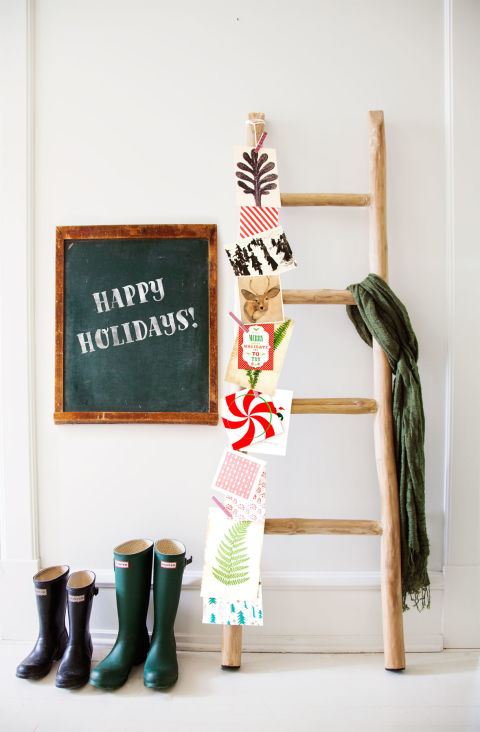 An old orchard staple becomes a fruitful holiday display with season's greetings (secured with clothespins attached to a string) in this Tudor home's living room. A chalkboard provides a spot for well wishes.