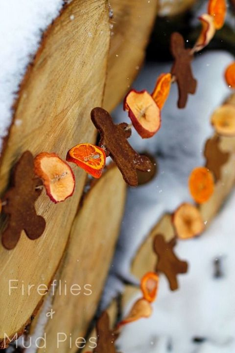 Invite your children to join in on making this fun, vintage holiday garland! First, bake thin slices of fruit in the oven. For the gingerbread men, mix cinnamon, cloves, and applesauce into a pliable clay. Once everything has dried, string the pieces on a strand of twine. 