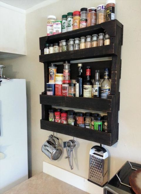 Isn't it amazing that a coat of black paint takes an average pallet from rustic to sleek almost immediately? Even better: This wooden shelving unit features four shelves for spices — not to mention hangers for a cheese grater and more below. See more at Pallet Furniture DIY »