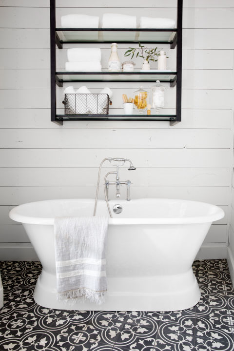 """""""As much as I love white subway tile and white shiplap, I know when there's too much white in a space. This floral tile is bold, but the black color keeps it feeling classic. The open metal shelves above the tub give the room a touch of 'modern farmhouse' that you see throughout the home."""""""