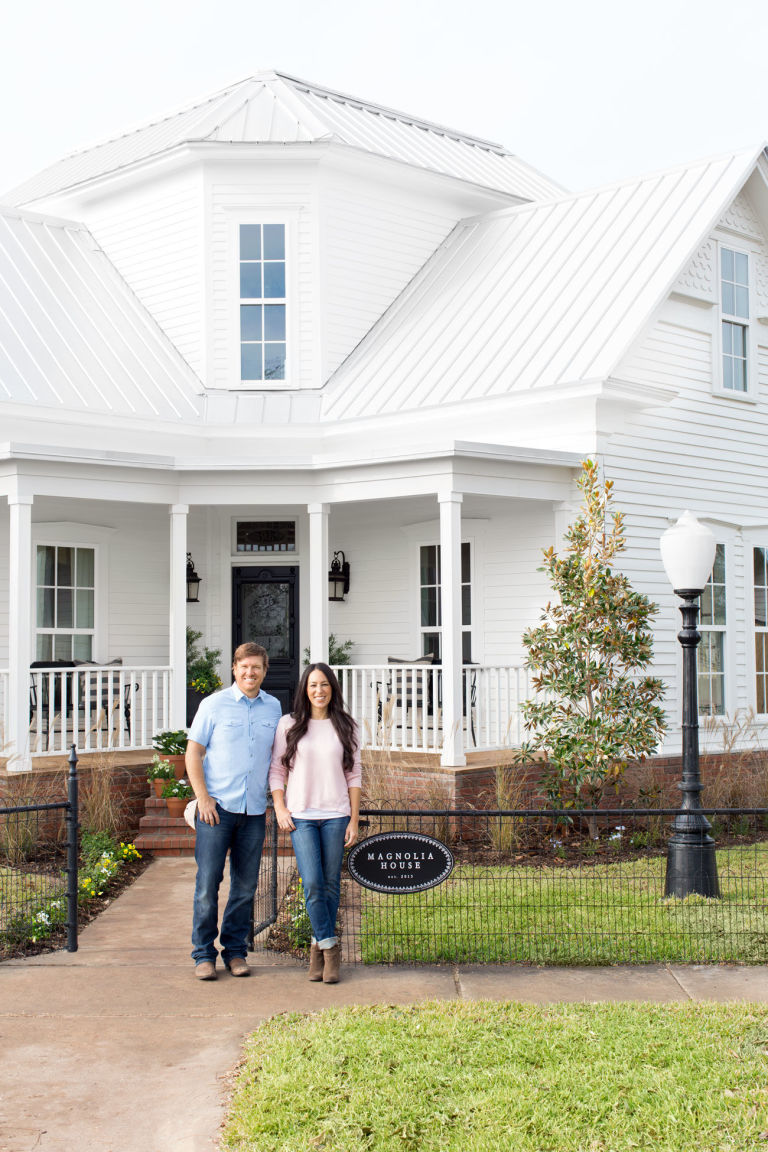 Happily married husband and wife: Chip and Joanna Gaines in front of their beautiful white house
