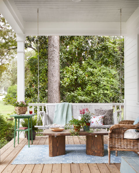 An antique porch swing turns this front porch into a cozy outdoor sitting room.