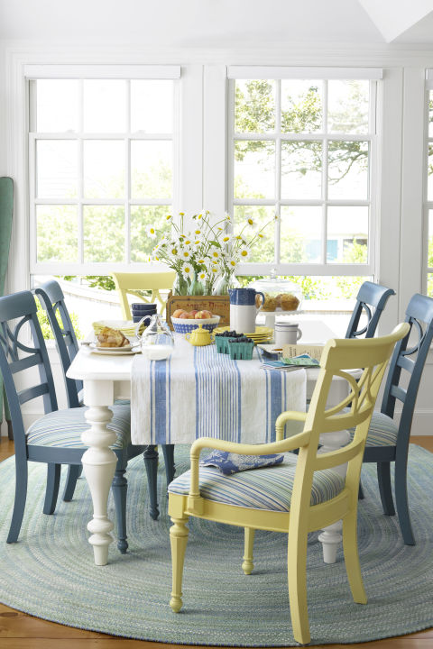 """This breakfast nook has a beachy, barefoot quality—underscored by a braided rag rug, deliberately mismatched seats, and a pair of oars leaning in one corner and painted a color similar to """"Treasure Isle"""" by Olympic. A crate full of glass bottles offers a foolproof way to arrange flowers."""