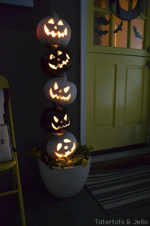 "For this easy Halloween project, prime five pumpkins, spray paint three white and two black, and drill 1"" holes into each. Alternating colors, place the pumpkins onto a dowel that stands in the middle of a flower pot. Thread lights through for a top-notch topiary. 