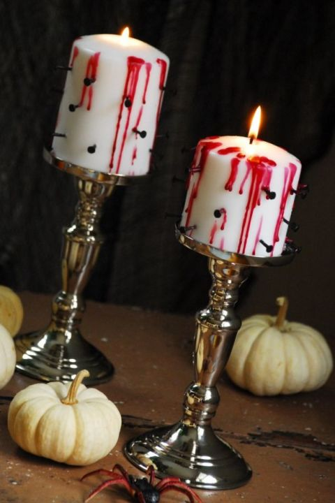 Pierce ordinary candles with black carpet tacks and drip red wax down the sides for tortured candles that take only five minutes to make.  