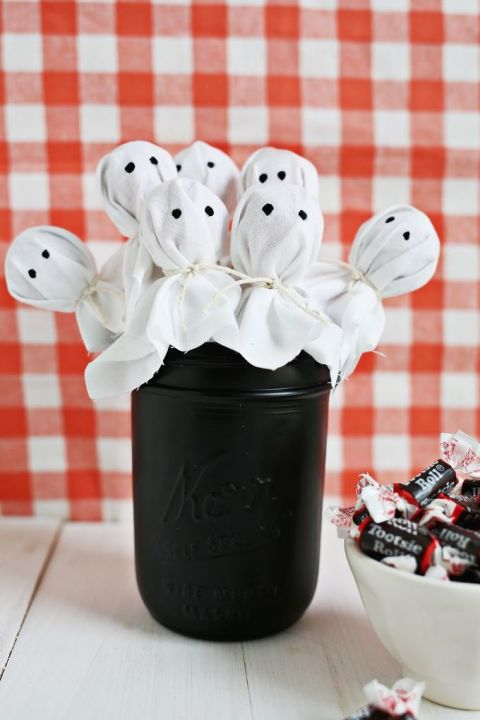 Drape white cotton over lollipop candies, tie with twine, and paint on black eyes for this ghostly edible centerpiece. 