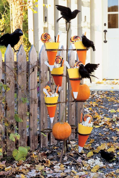 """Halloween entertaining is all about scaring up creative ways to celebrate the holiday. Neither children nor grown-ups want to miss out on trick-or-treating. Treat every guest to a surprise right at the door, perhaps with candy-filled cones nestled in a vintage plant stand aflutter with feathered crows. Candy Cone How-To: 1. To create a cone about 10 inches long, first wrap an 8 1/2"""" by 11"""" sheet of heavyweight white paper on the diagonal. Trim excess paper. Use this as a template to cut as many cones as desired. 2. Shaping each cone according to the template, use pinking shears to cut a band of glossy orange paper about 4 inches wide for the middle of the cone, and a band of yellow paper about 3 inches wide for the top. Affix the orange and yellow bands to the white base, then join the ends of the cone together, using double-sided tape."""