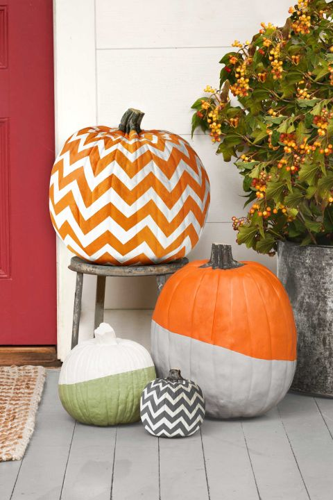 You can create all of these nifty designs using acrylic paint and painter's tape.  For a two-tone, dipped look, bisect a pumpkin with a strip of tape (angle the tape for a diagonal effect). Use a foam brush to cover one section of your pumpkin with two coats of acrylic paint, allowing 30 minutes of drying time per coat. Remove the tape and discard. Stop there, or repeat the steps to add another color to your pumpkin.  To form chevron stripes—whether two or tons—link short strips of tape to make the zigzag patterns, using our photo as a guide. Use a foam brush to cover your pumpkin with two coats of acrylic paint, allowing 30 minutes of drying time per coat. Remove the tape and discard. Clean up the edges with a cotton swab if necessary. If you'd like the second color to be different than natural pumpkin orange, fill in using a small paintbrush and contrasting acrylic paint, as we did for the black-and-white pumpkin.