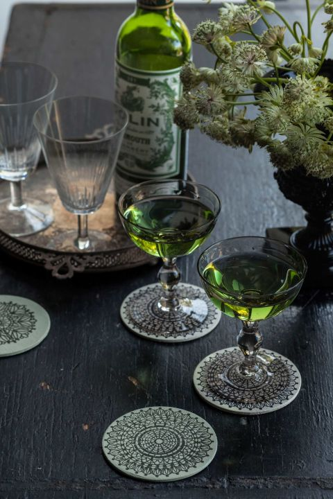 The secret to this inviting witch's brew? Gin, vermouth, and a couple drops of green food coloring. Glasses can rest in lovely peace on these coasters. Here's how to fashion your own: First, paint both sides and the rims of three-inch wooden disks ($6 for 25; craftparts.com); we chose Farrow and Ball's Green Blue and Golden's Titan Buff. Once the paint's dry, stamp on a crochet motif ($7.99 for acrylic mounting block; amazon.com), using a black solvent ink pad like Tsukineko's StazOn ($7.75; amazon.com). Let the ink dry for five minutes, then seal with a matte finishing spray.