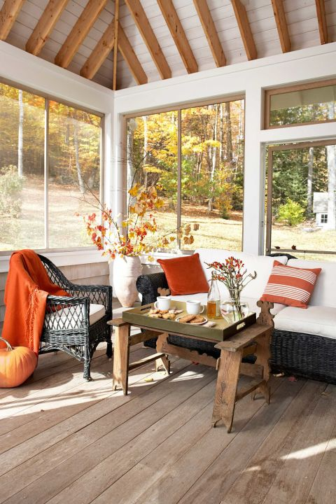 Wicker pieces, accented with burnt-orange accessories, offer seating on this glassed-in porch. The off-white urn is a TJ Maxx score.
