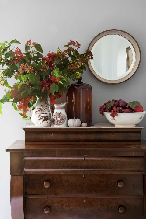 The owner of this New Jersey home displays fall foliage in transferware atop a 19th-century mahogany dresser in her dining room.