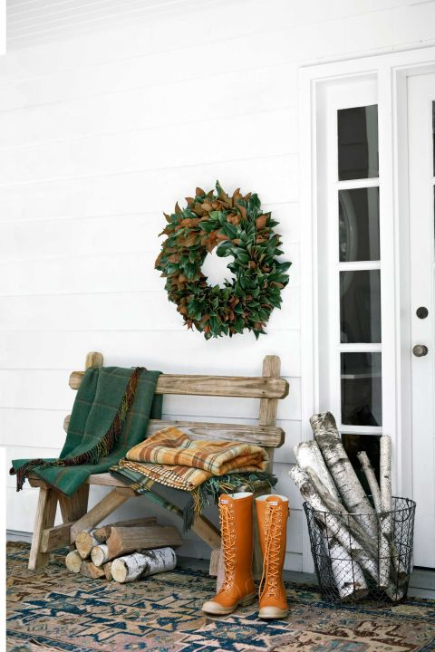Country Willow throws and a wire basket filled with firewood adorn this front porch.
