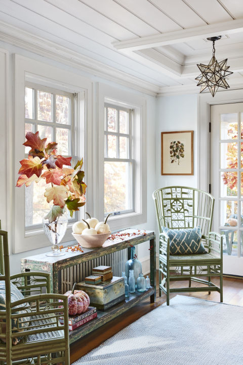 "The barely blue paint color in this living room provides a breezy backdrop for a little sweep of something from the garden—like this oakleaf hydrangea—and understated white ""Baby Boo"" pumpkins."