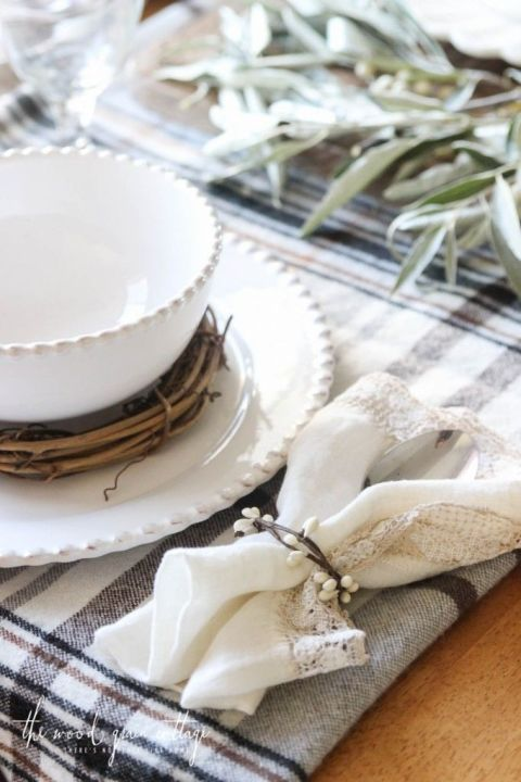 White dishes, DIY napkin rings, and branches with berries combine to make a fall-themed dinner table. 