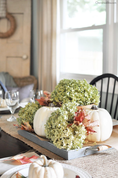 Place white pumpkins, dried hydrangeas, and fallen leaves on a tray to create a portable centerpiece. When your dining room table isn't in use, move the tray to a fireplace or entryway table. 