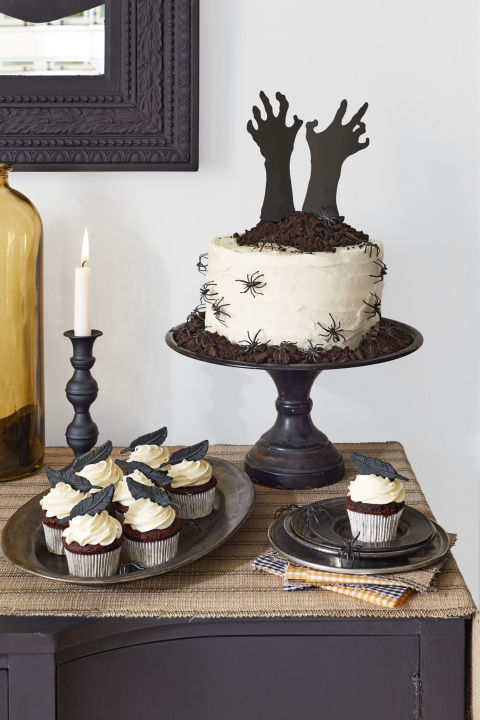 """The eye-catching """"Help Me!"""" cakeis simply a store-bought white cake with a few dark twists. (Talk about hands-off!)Start with a store-bought frosted layer cake. Cut out a pair of arms and hands in black craft paper and tape to skewers to help them stand upright. Pile on a mound of """"dirt""""— crumbled chocolate cookies—to give it that """"buried alive"""" vibe.Top vanilla-frosted cupcakes with edible fondant raven feathers (piratedessert.etsy.com).For an extra hair-raising element, add plastic critters around the cake."""