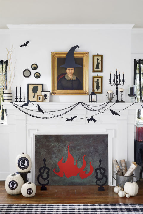 "Adorn old portraits and silhouettes with witch hats, pitchforks and scythes, fangs, and devil horns. Detailed cutouts of candelabras and sticks, ""lit"" with gold flames, give a mantel faux glow. Trick out the perfect mantel decor with paper bats attached to swoops of black sewing trimming with black upholstery tacks. Finally, line the opening of your fireplace with paper or painted wood, and attach a roaring red paper glow. Cut snake andirons from black foam core and glue to painted craft blocks."