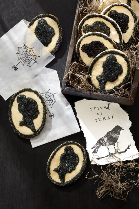 "Cameo cookies make for a spooky-sweet party favor. Use a silhouette-shaped cookie cutter (fancyflours.com) to cut the cameo outline from slice-and-bake sugar cookie dough; bake as directed. Once cool, apply white royal icing to the portrait and ""frame,"" then coat with sparkling black sanding sugar (shopbakersnook.com), shaking off any excess."