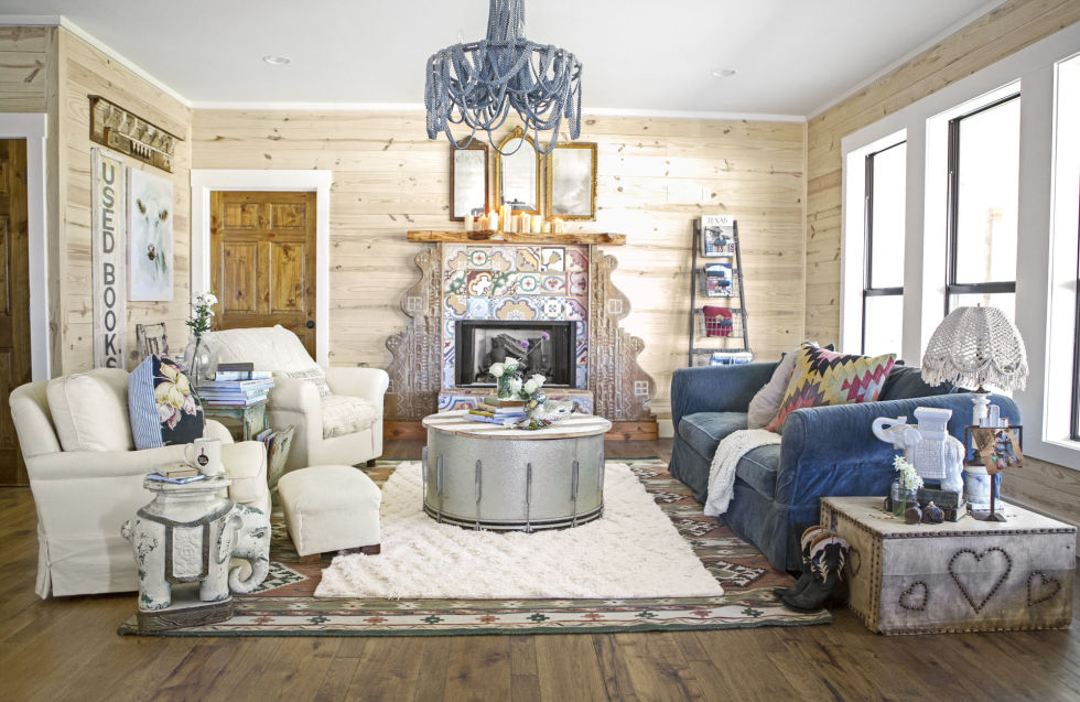 "In this living room, a piece of dead cedar, a massive 1920s corbel, and mismatched tile makes for a dramatic focal point. In addition to the fireplace, the coffee table is a bass drum topped with salvaged wood. ""We love that you can take 'leftovers' from some old place and turn them into magic,"" says Amie Sikes of the ""Junk Gypsies."""