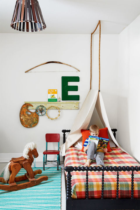 From the ropecanopyto the nautical rug, this whimsicalkid's room belongs in a breezy summer homewith its bright colors and vintage touches, like the oversized plastic E and red-and-blue chair.