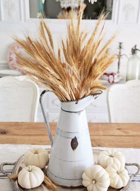 Use an antique pitcher as a vase to hold faux wheat. Add neutral-colored pumpkins at the base of the pitcher to complete the look.