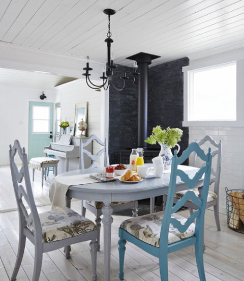 A single chair accented in bright blue adds a pop of color and visually connects it to the adjoining blue-and-white living room of this Alberta farmhouse.<br />