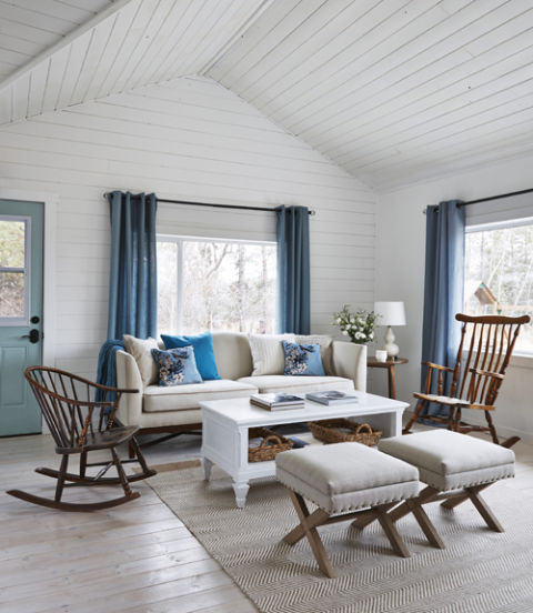 So the interior didn't compete with views of the farm, the owner of this Alberta farmhouse opted for crisp white paint on the walls and ceiling, and blue draperies that complement the large stretch of sky outside the windows. Light pine floors with a single coat of whitewash allow the wood's natural grain to show without taking away from the room's airy feel.