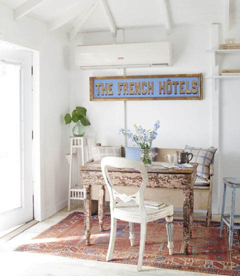 8. Incorporate versatile antiques. One reason Fifi loves vintage pieces: They can be used in more than one way. Take the salmon-hued table she uses as a desk and an old church pew outfitted with feather-down pillows. In a pinch, the arrangement easily transitions to an extra dining space. Another example? A graphic vintage hotel sign draws attention away from the hardworking heat and air wall unit. 9. Take it to the rafters. This portion of Fifi's home came with vaulted ceilings, which add another 4 feet to the ceiling height and help her office feel airy in spite of its modest footprint. An HVAC wall unit keeps the area cool—no space-reducing ductwork required! RELATED: 26 Easy and Efficient Home Office Ideas