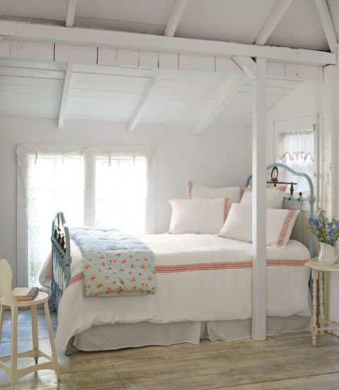 10. Embrace beds in front of windows. Fifi tucked her queen-size bed—a blue cast-iron number she fell in love with at a local antiques shop—in front of not one, but two windows to free up other wall space for storage pieces. The unconventional placement enhances the cozy factor without blocking light. 11. Stick with simple bedding. Set against the white walls and floors, Fifi's mostly white pillows and duvet cover establish a cohesive, not choppy, look and serene vibe. Meanwhile, a few red stripes and a floral coverlet add just enough pattern to keep the room from feeling lifeless.