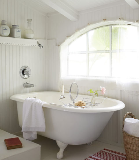 14. Consider a soaking tub. The bathroom's pitched ceilings made a standard-height shower a no-go, so Fifi chose a deep cast-iron bathtub instead. To keep costs down, she purchased a dilapidated tub for $100 at a junkyard and then had it refinished. 15. Let in the light. A yard of cheesecloth strewn from Shaker pegs above the window creates just enough privacy without blocking natural light in the small space. The gauzy fabric also adds a soft, feminine finish that complements the tub.