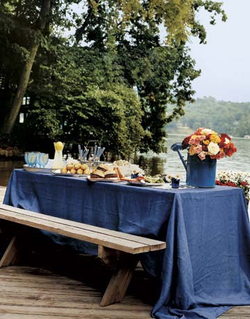 Uncomplicated yet refined is the philosophy at this outdoor fete. Vibrant colors — in the flowers, the tableware, even the food — enhance the lush lakeside setting. A simple cotton tablecloth and summer flowers dress up the food-laden picnic table with a minimum of effort.