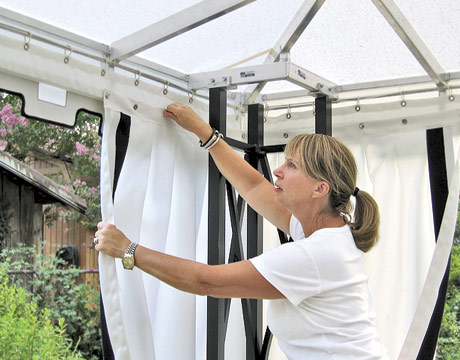 Woman Installing Curtains On Patio