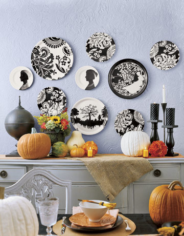 black and white graphic plates on a wall above a halloween decorated table - Halloween Table Decoration