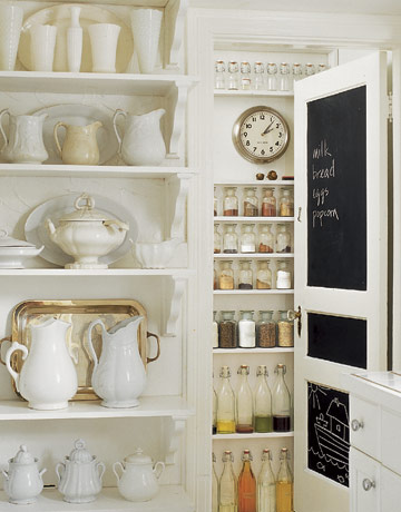 Kitchen Pantry With White Pitchers On Shelves And Bottles And Jars Filled With Spices