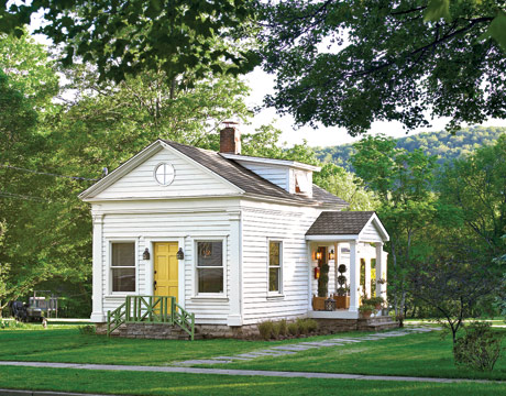 a small white cottage with yellow door surrounded by trees - Cottage Design Ideas