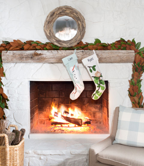A brown-and-green garland adds a stark contrast to an all-white fireplace.  Tour the home: A Calming Christmas in a 1970s Atlanta Farmhouse