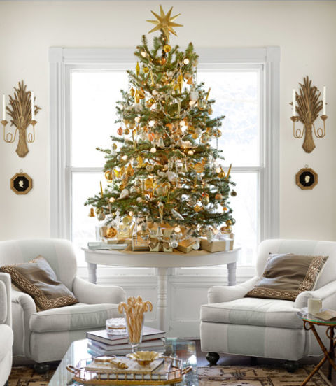 Instead of one grand tree, place multiple mini-trees throughout the house. This one, on the library's demilune table, jibes with the room's palette. RELATED: A Colorful New England Christmas with Eddie Ross