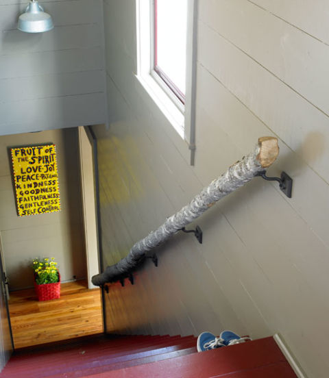This handrail—made from an oak log cut on the property—lends a woodsy touch to the stairs leading down to the game room. The folk-art sign was bought at a local shop.