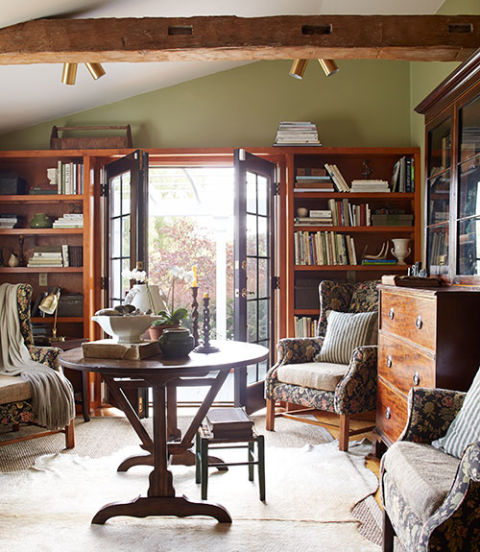 In the library of this New York home, the owner unified mismatched wingback chairs with floral brocade upholstery and burlap cushions. The walls are painted Spanish Moss by Restoration Hardware.
